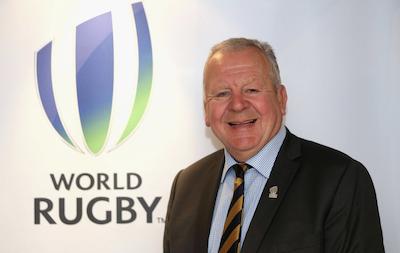Bill Beaumont im Anzug blickt in die Kamera vor einem World-Rugby-Logo stehend.