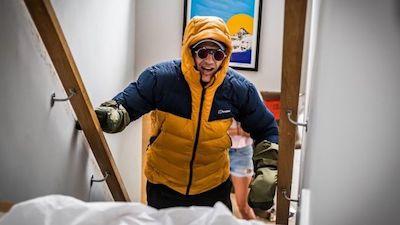 Ed Jackson steht im Expeditions-Outfit auf der Treppe und zieht sich hoch.