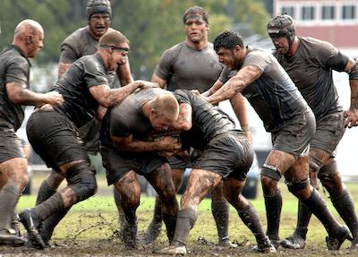 Rugbyspieler kämpfen im Schlamm um den Ball