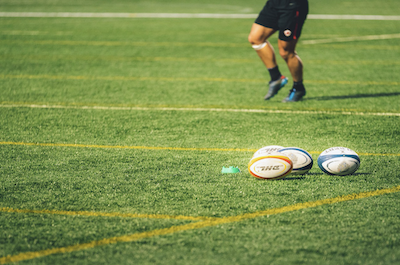 Vier Rugbybälle auf dem Spielfeld mit Spieler im Hintergrund.